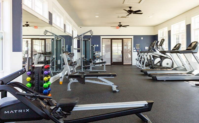 Large gym with large windows and a rowing machine