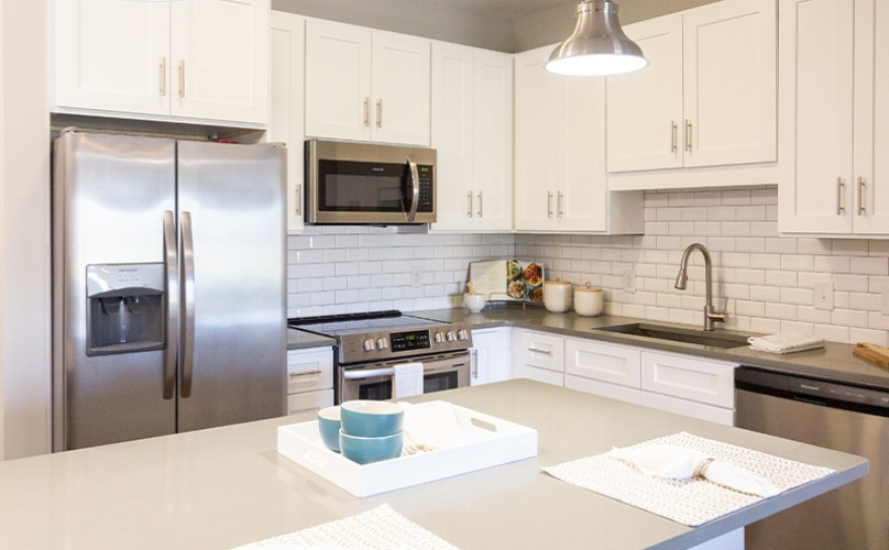 Spacious well lit kitchen with white cabinets and stainless steel appliances.