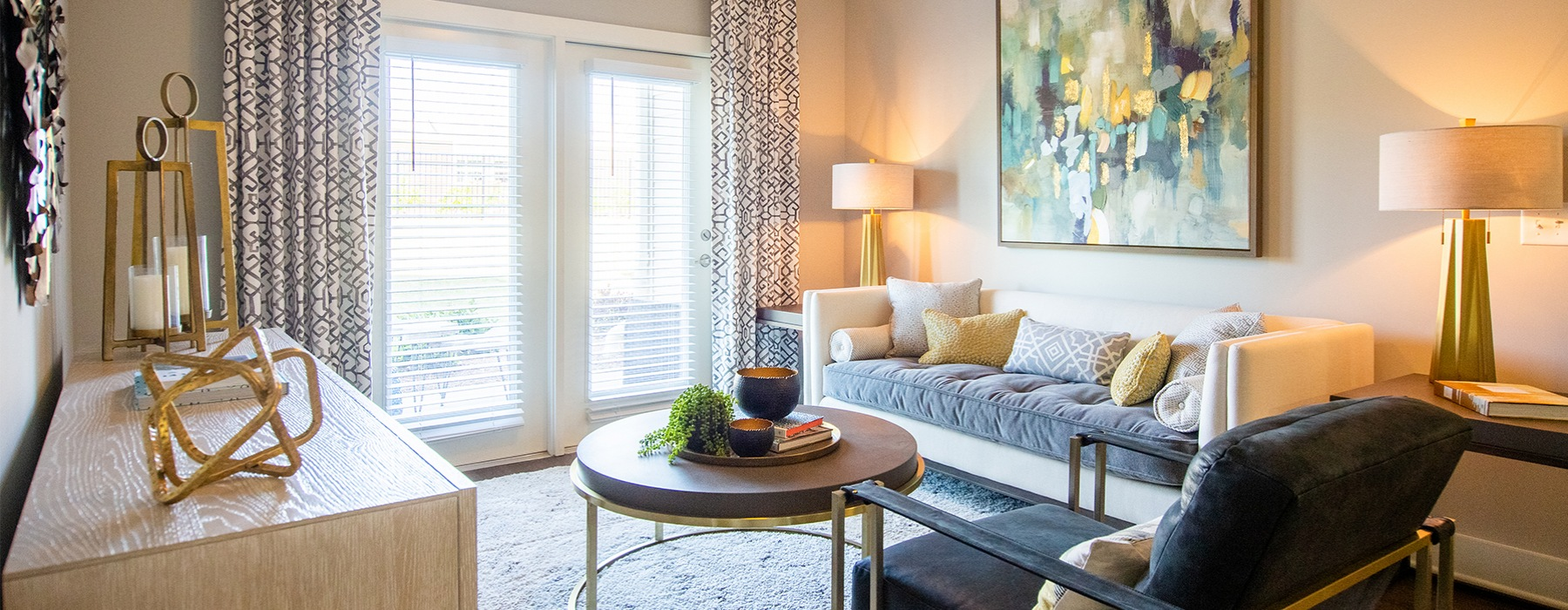 Spacious well lit living room with large french doors and beige walls.